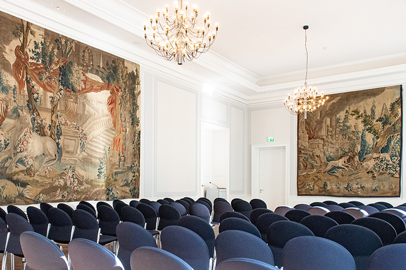 View of the Gobelin Hall of the Old Town Hall in Bonn, woven tapestries, chandeliers on the ceiling and blue rows of chairs.