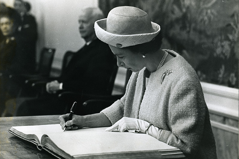 Black and white photograph of Queen Elizabeth II, signing the city's Golden Book in Bonn's Old Town Hall