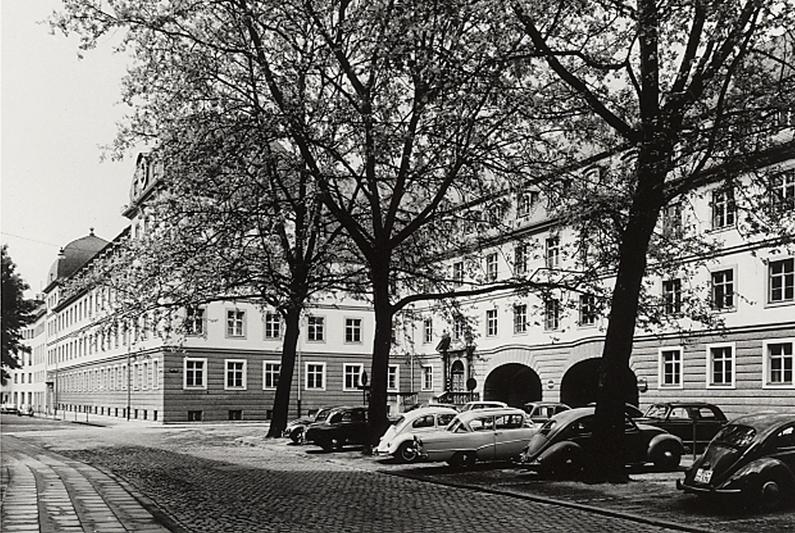 Hinter Bäumen und mehreren Autos ist das alte Stadthaus in einer Aufnahme von 1962 zu sehen.