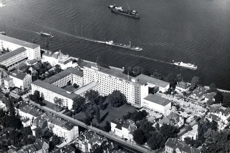 Black and white photography, aerial view of a tall building next to a river bank