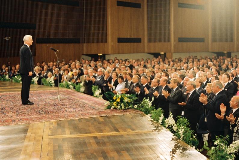 Richard von Weizsäcker auf der Bühne in der Bonner Beethovenhalle, am Mikrofon stehend und festlich gekleidet, das Plenum applaudiert