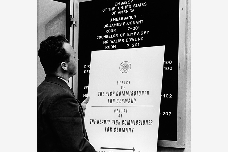 "Black and white photography, a man exchanges the information board of the US-American High Commissariat for one with the imprint ""Embassy of the United States of America""."