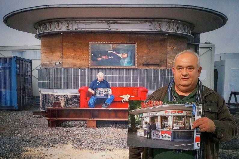 Ein älterer Mann hält ein Foto des Kiosks an seinem alten Standort hoch, im Hintergrund ist der Kiosk mit verbarrikadierten Fenstern auf einem Bauhof zu sehen.