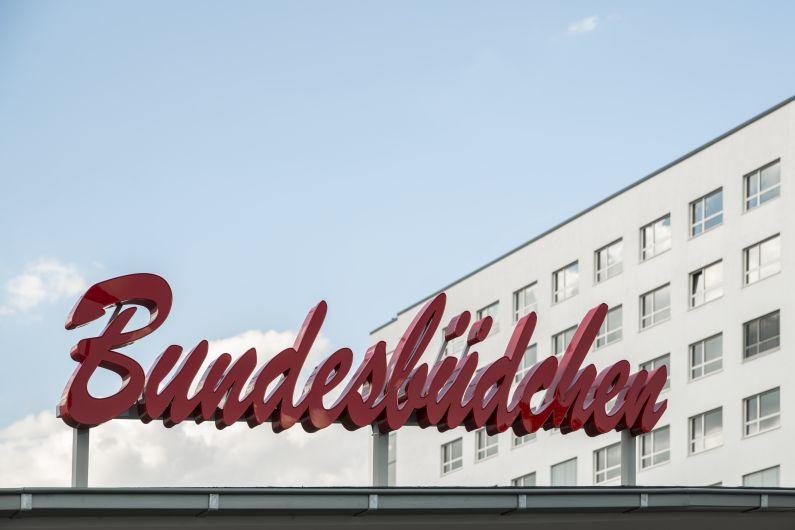 Der rote, geschwungene Schriftzug auf dem Dach des Bundesbüdchens in Nahaufnahme.