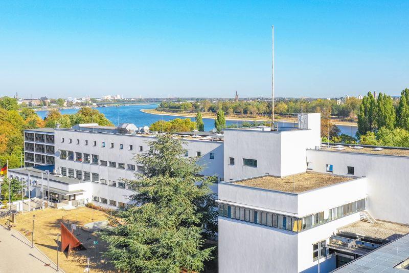 Luftaufnahme, weißer, kastenförmiger Gebäudekomplex, vierstöckig, Deutschland-Fahne am Eingang. Hinter dem Gebäude ist der Rhein zu sehen.