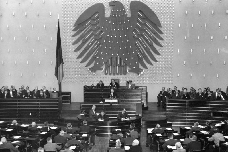 Schwarzweiß-Fotografie, vollbesetzter Sitzungssaal, mittig das Rednerpult, großer Bundesadler an der Wand, Deutschlandfahne links.