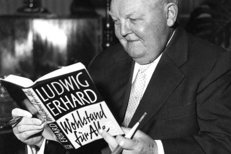 Black and white photograph by Ludwig Erhard, who is leafing through his book in his office.