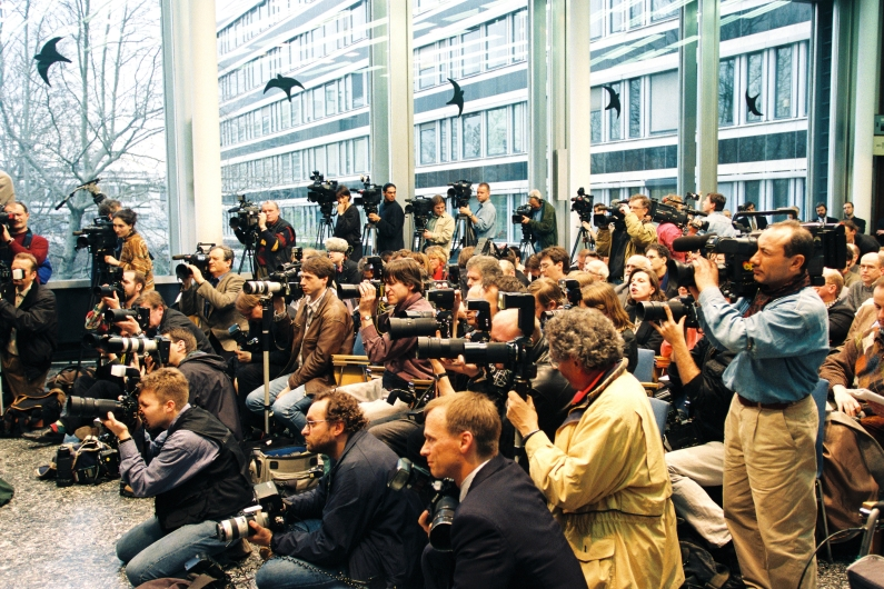 A large group of journalists in the press room of the Federal Press Conference in Bonn, sitting on several rows of chairs, equipped with numerous cameras.