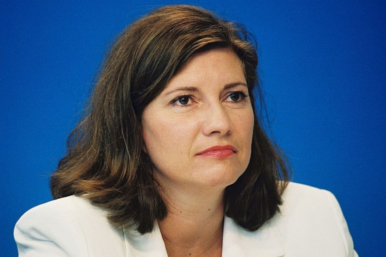 Portrait photography of Charima Reinhardt against a blue background.