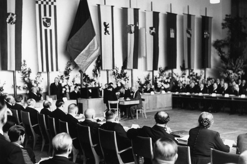 Black and white photography, plenary hall with lectern and members of the Bundesrat, on the wall the flags of the federal states of Germany.