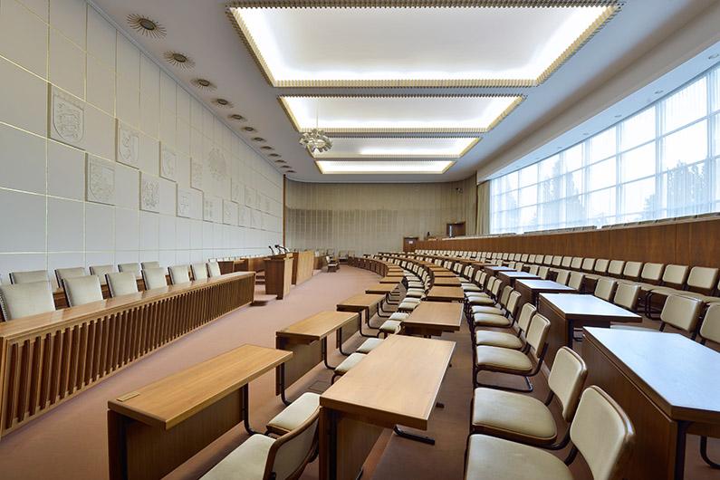 Blick seitlich auf leere Sitzreihen im Plenarsaal des Bundesrats, rechts eine große Fensterfront, links das große Rednerpult.