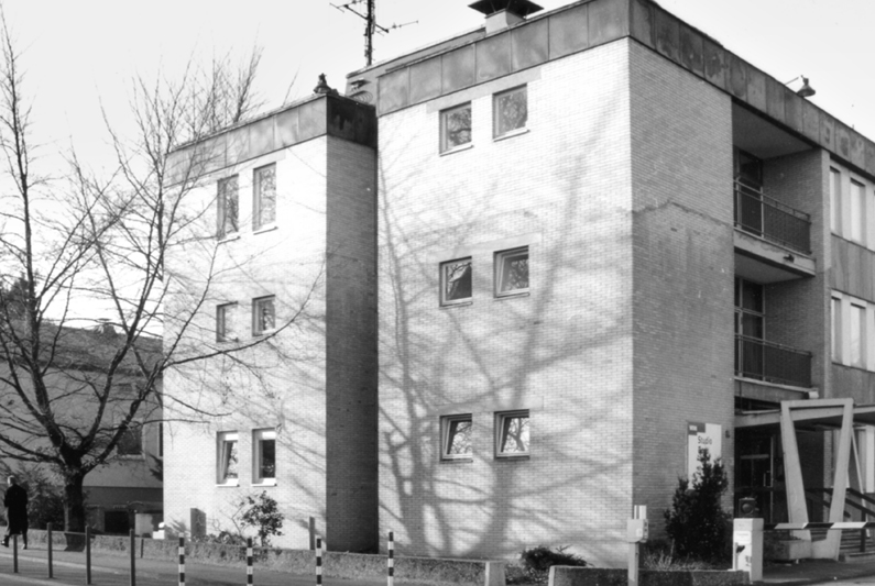 Black and white photograph of a simple, three-storey flat-building with small windows and a tree in front of it.