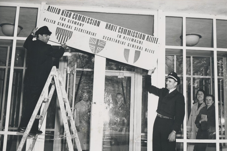 Black and white photograph, a man on a ladder removes the signage at the entrance of the US High Commission.