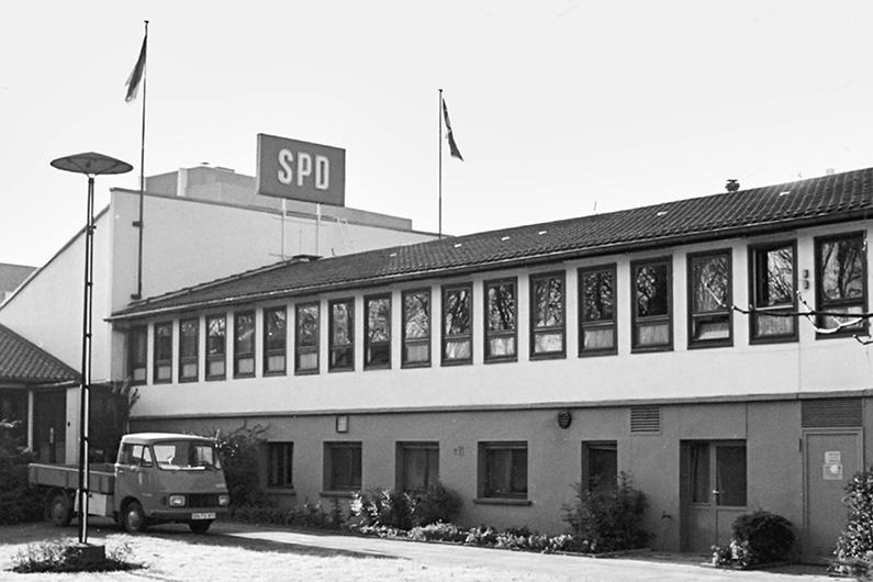 """Schwarzweiß-Fotografie, Blick auf die SPD-Parteizentrale """"Baracke"""", dem Vorgängerbau des Erich-Ollenhauer-Hauses, Gebäude in schlichter und flacher Fertigbauweise, darüber das SPD-Logo"""