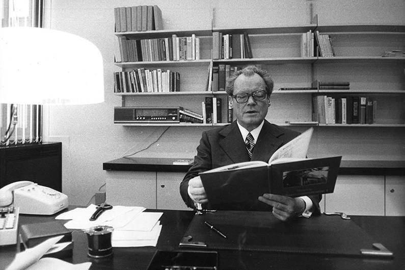 Black and white photography of Willy Brandt in his office, sitting at his desk with a book in his hand, behind him several shelves, on his desk a telephone and documents.