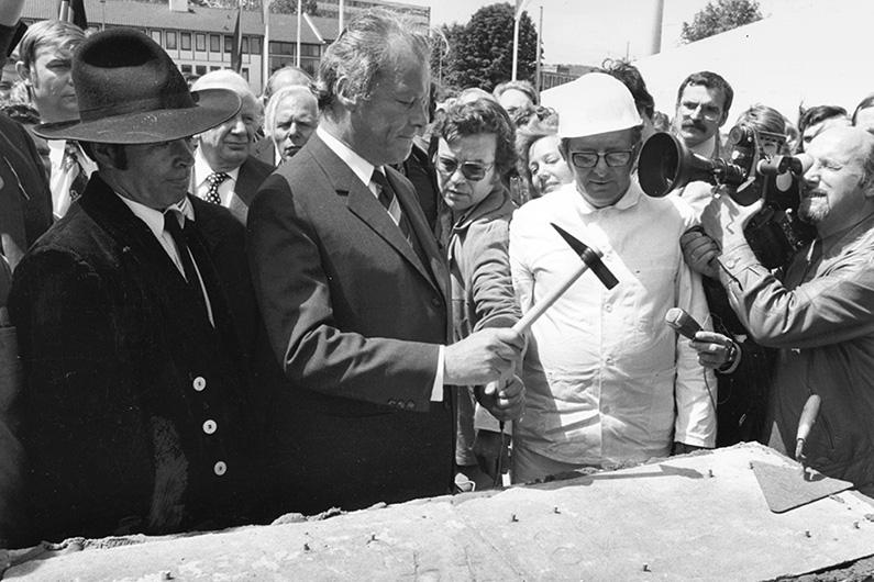 Schwarzweiß-Fotografie, Willy Brandt (mittig) bei der Grundsteinlegung des Erich-Ollenhauer-Hauses in Bonn, Pressevertreter filmen die symbolischen Hammerschläge Brandts mit dem Grundsteinhammer.