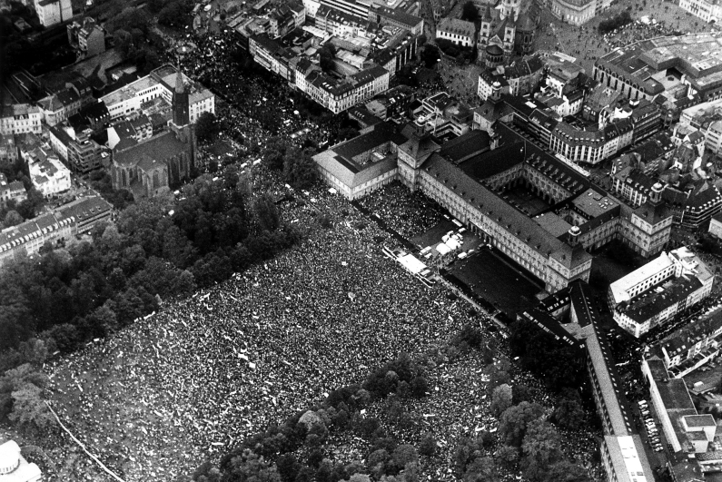 Black and white aerial photograph, view of the Bonn Hofgarten, filled with peace demonstrators, in front of the University of Bonn.