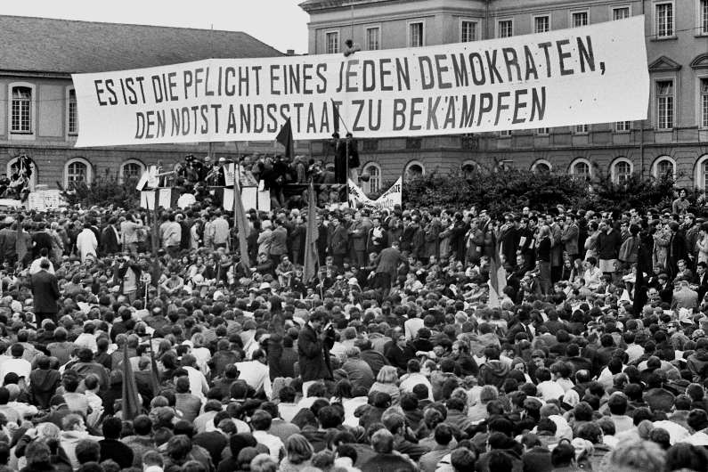 "Demonstrators gathering at Bonn's Hofgarten, above them a large poster with the inscription ""It is the duty of every democrat to fight the state of emergency""."