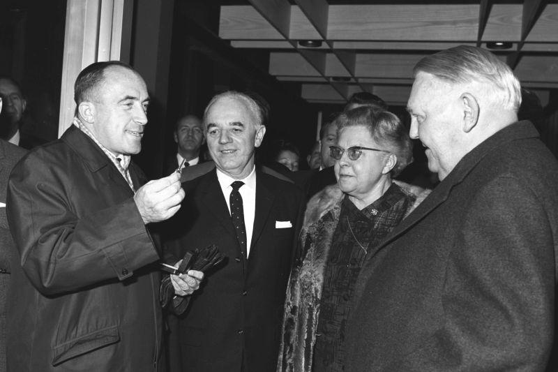 Schwarzweiß-Foto, drei Männer und eine Frau. Rechts steht Bundeskanzler Erhard und empfängt einen Schlüssel von dem Herrn links.