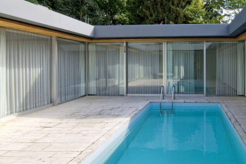 Kleines Schwimmbecken im Innenhof eines Bungalows mit verglasten Wänden.
