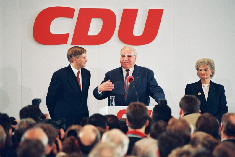 CDU Secretary General Peter Hintze (left), Chancellor Helmut Kohl (centre) and Hannelore Kohl (right) at Konrad-Adenauer-Haus in Bonn, behind them a red CDU logo on the wall.
