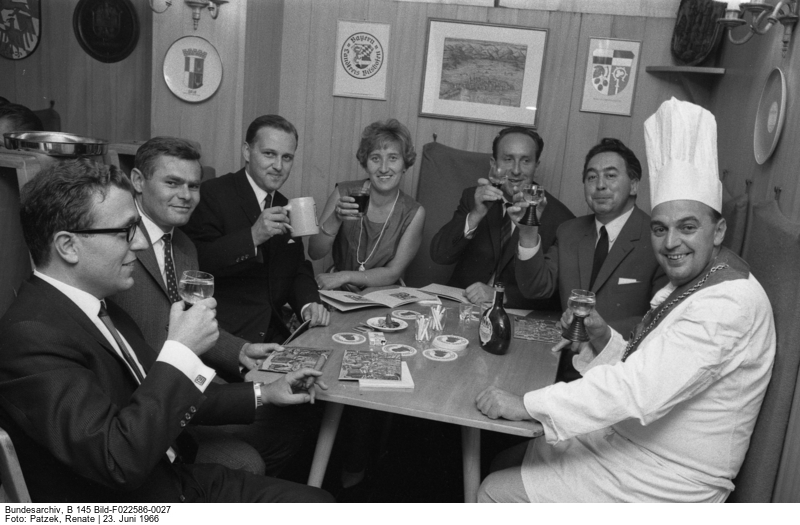 Seven people around a table with beer and wine glasses, cheering to the photographer