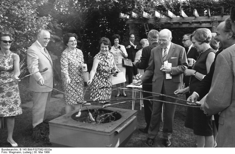 Several people around a barbecue grill where they grill sausages on sticks.