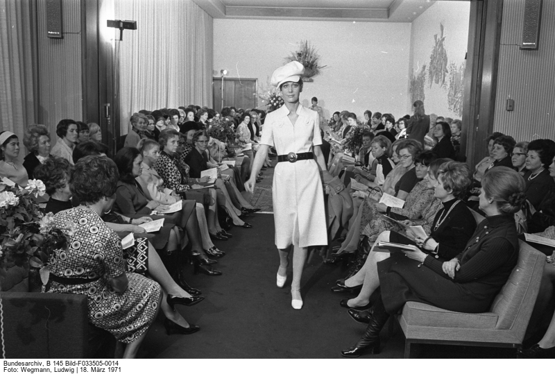 A model in the middle of a catwalk surrounded by a female audience. The model is wearing a white outfit with a hat