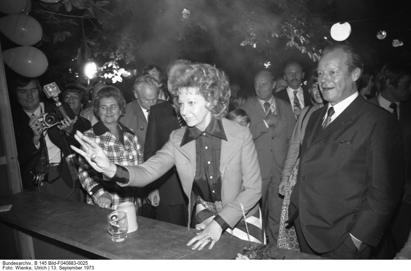 Rut Brand tossing a ball at a ball toss booth, next to her Willy Brandt.