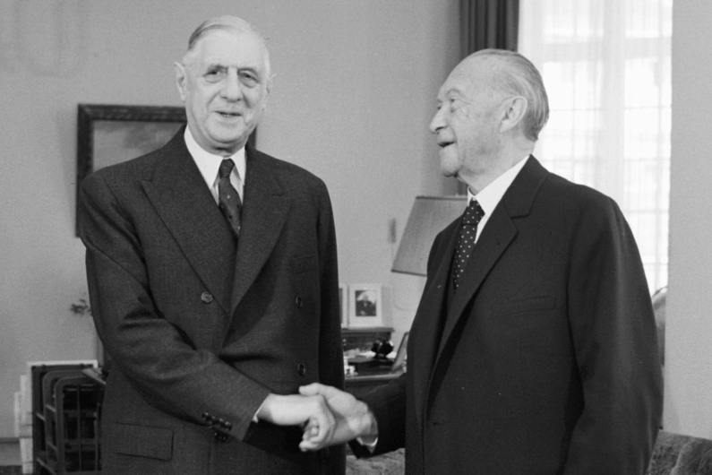 Konrad Adenauer and Charles de Gaulle in suits, standing in Adenauer's study and shaking hands.