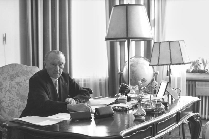 Black and white photography, Konrad Adenauer sits at his desk and looks into the camera.