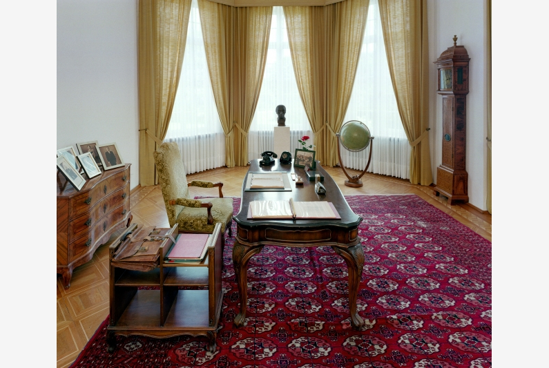 Study with desk and wooden furniture, a red woven carpet and large bay windows.