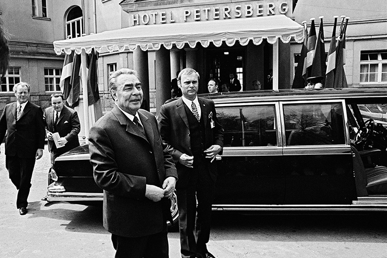 CPSU General Secretary Leonid Brezhnev in front of a black limousine, behind him the entrance of the Petersberg Hotel.