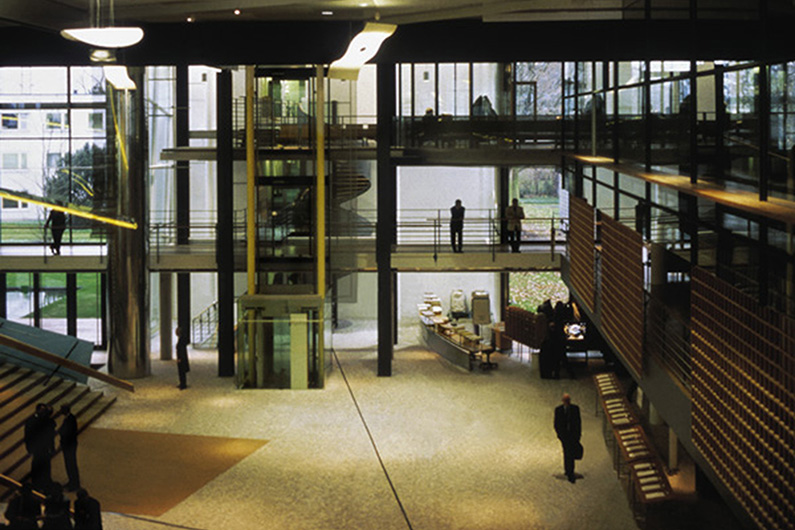 View into the generous entrance area of the Bundeshaus, large glass windows, light-coloured floor, a glass elevator in the middle, a wide wooden staircase to the right of it.