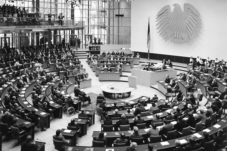 Black-and-white photography, view of a filled plenary hall with round seating arrangement, bright and transparent architecture, a lectern in the middle of the hall, on a wall the Federal Eagle