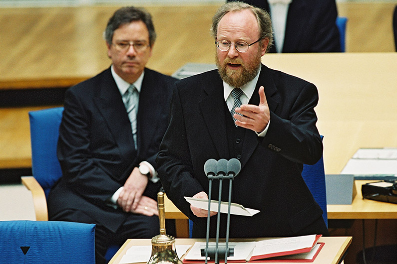 Wolfgang Thierse standing at the lectern of the plenary hall of the Bundestag in Bonn, in front of him a microphone.