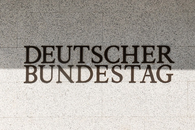 "View of a sandstone coloured wall with black lettering ""Deutscher Bundestag"" (German Bundestag)"