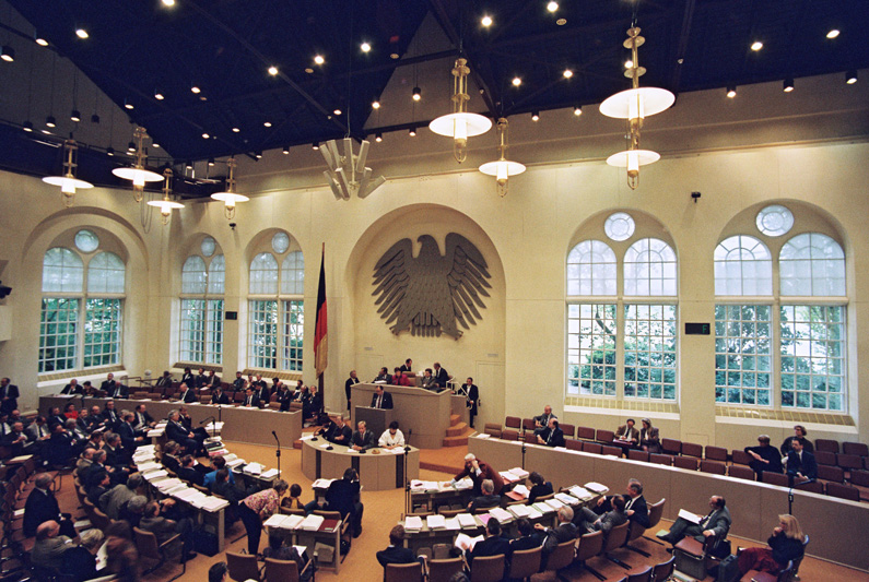 """View of the first all-German Bundestag in the plenary hall of the """"Wasserwerk"""" in Bonn, the parliamentarians in a circular seating arrangement, the lectern in the middle, behind it a wall with a large federal eagle and decorative windows."""