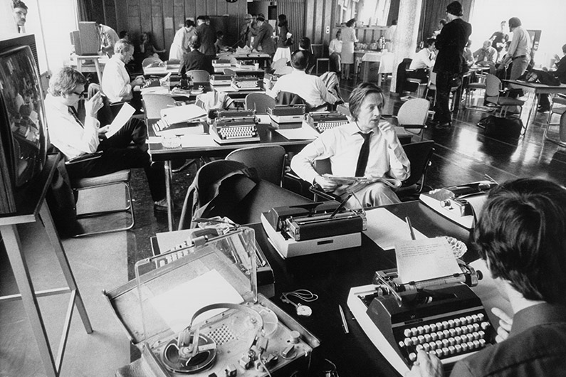 Black and white photography, journalists in an office, sitting at desks with typewriters.