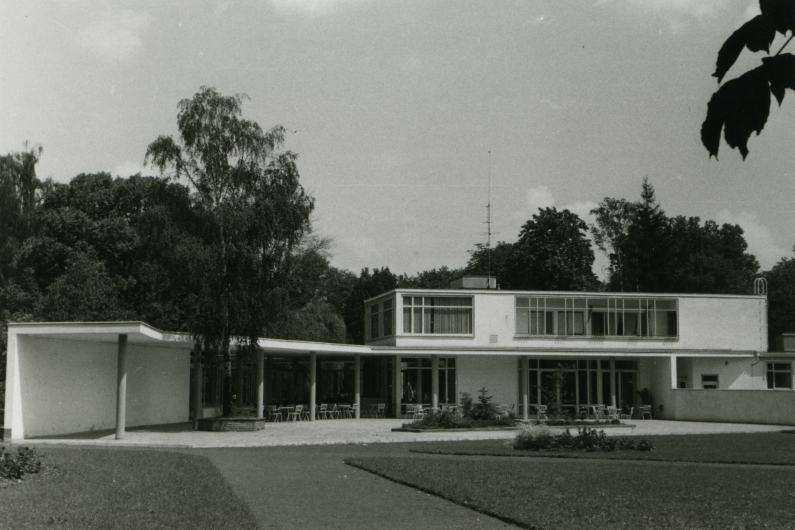 Black and white photograph of a pavilion-like part of the Stadthalle Bad Godesberg, garden chairs and lawn in front of it.