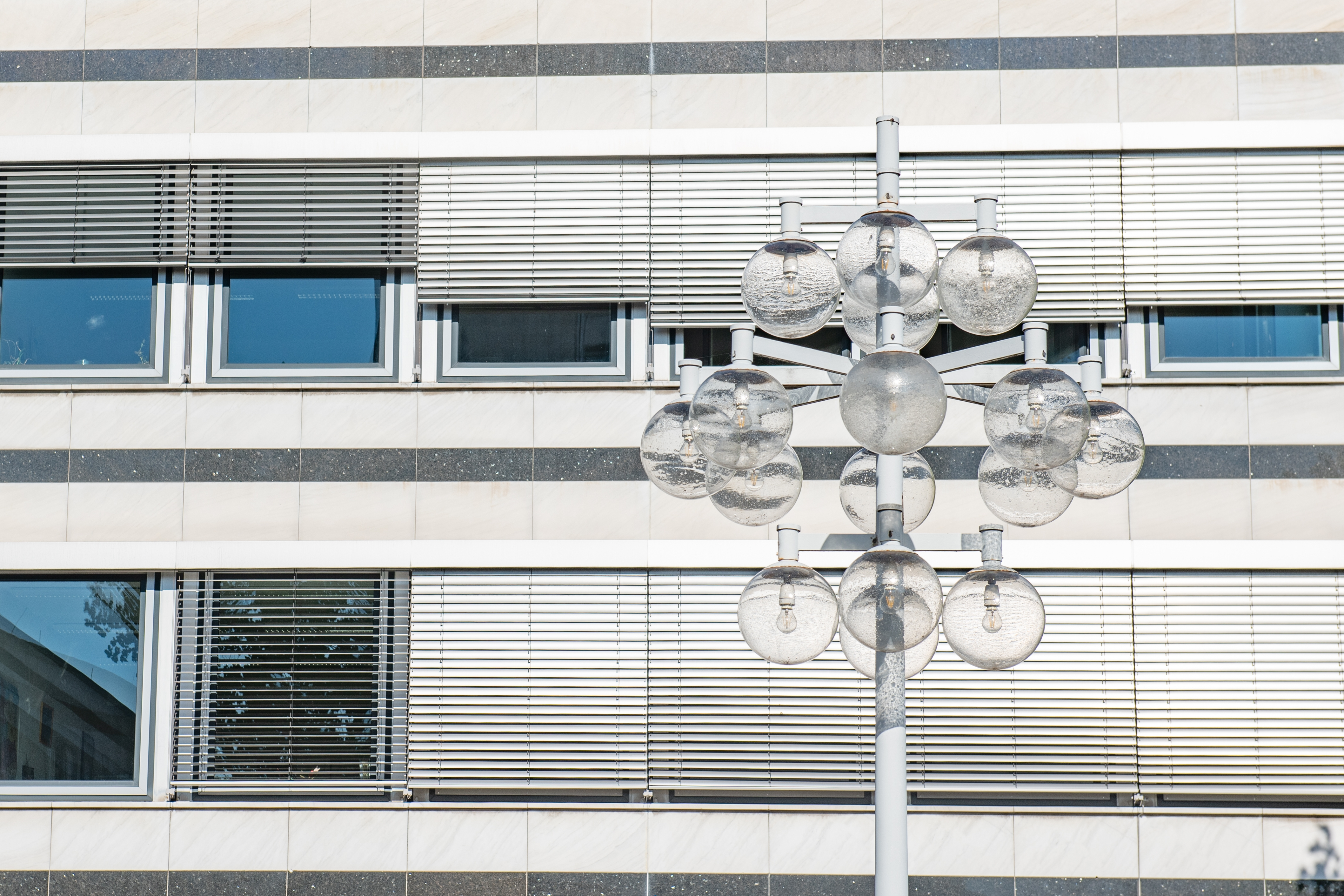Office window with blinds, in front of it a striking street light with numerous round glass lights.
