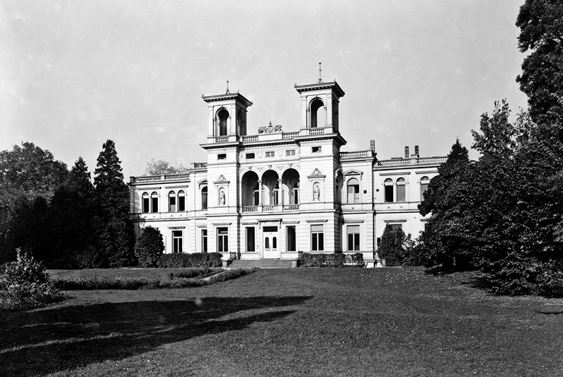 Black and white photography, white building, park in front.