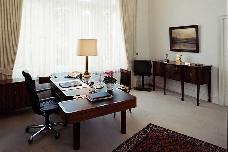 stilvoller Raum mit Schreibtisch aus dunklem Holz, einem Teppich und einer Kommode mit Blick auf ein großes Fenster