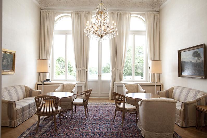 heller stilvoller Raum mit großem Orient-Teppich, darauf Sitzmobiliar im französichen Stil aus dem 19. Jahrhundert und ein Kronleuchter von der Decke hängend