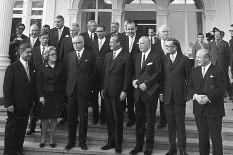 Schwarzweiß-Fotografie, eine Gruppe von Männern in Anzügen steht auf den Stufen eines weißen Gebäudes.