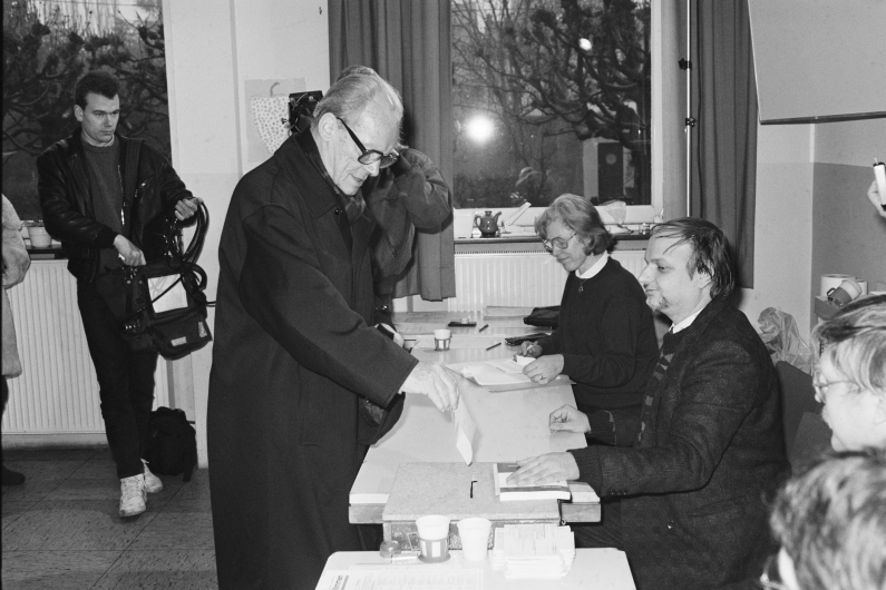 Black and white photography of Willy Brandt (SPD) throwing his ballot paper for the first all-German Bundestag election into the ballot box.