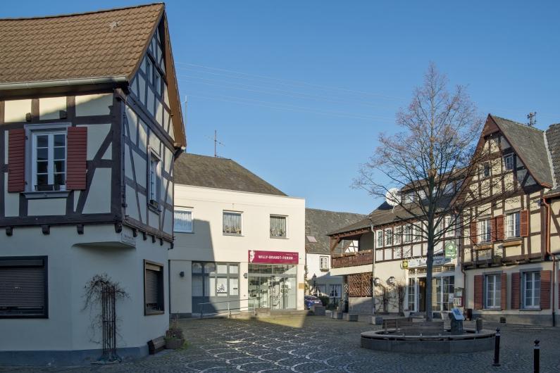 Unkeler Marktplatz mit Kopfsteinpflaster bei blauem Himmel, hinten mittig das Willy-Brandt-Forum, an den Bildrändern Fachwerkhäuser, vorne rechts ein Baum